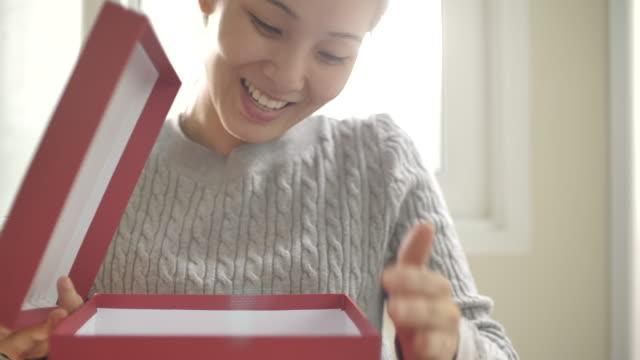 アジアの女性は、自宅で白い弓と開くギフトボックスを解き放つ - プレセントの箱点の映像素材/bロール