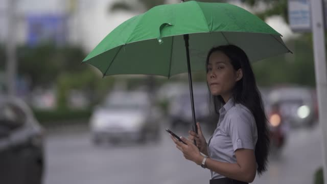 Asian woman use the umbrella while it rains She is walking across the street. And use the phone