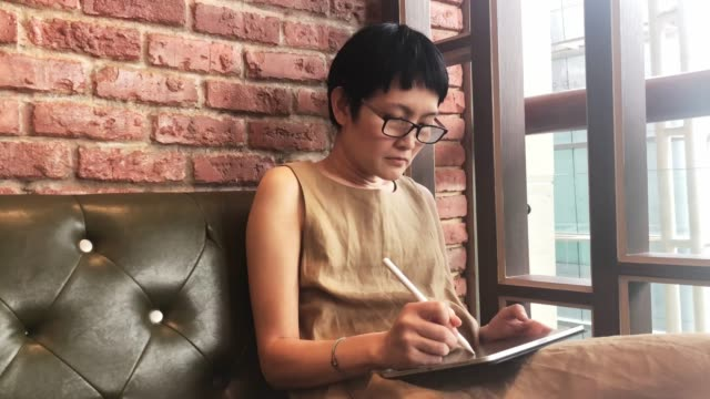 Asian woman using computer tablet in cafe