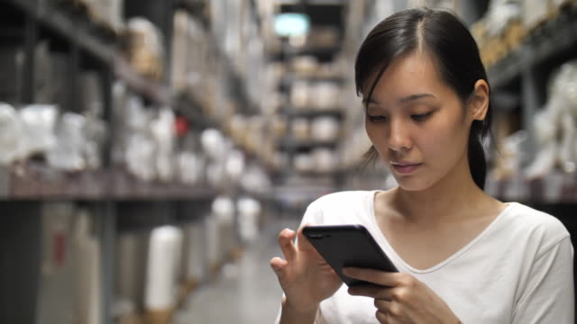 asian woman using digital in warehouse - ventenne video stock e b–roll