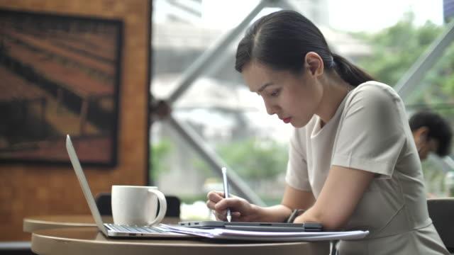 stockvideo's en b-roll-footage met aziatische vrouw met behulp van digitale tablet voor haar werken in cafe, met behulp van gedigitaliseerde pen - oost azië