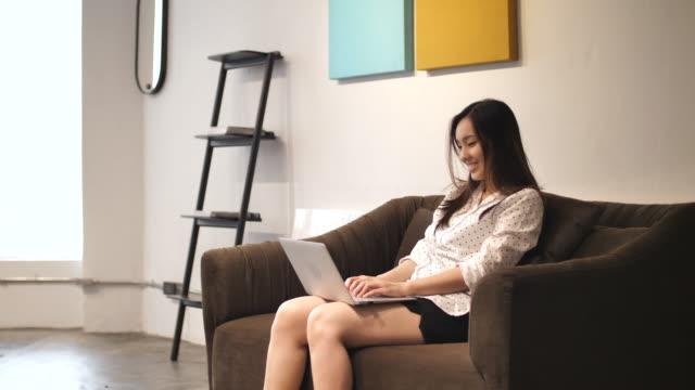 自宅でラップトップを使用してアジアの女性 - ソファ 女性点の映像素材/bロール