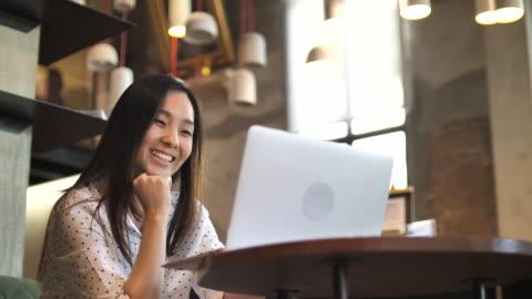 亞洲女人在咖啡館中,慢動作使用筆記本電腦 - laptop 個影片檔及 b 捲影像