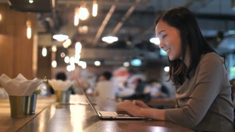 vídeos y material grabado en eventos de stock de mujer asiática usando laptop in cafe - parte del cuerpo humano