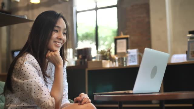asiatisk kvinna använder laptop i café - använda en laptop bildbanksvideor och videomaterial från bakom kulisserna