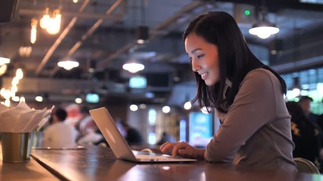 亞洲婦女在咖啡館使用筆記本電腦 - cafe 個影片檔及 b 捲影像