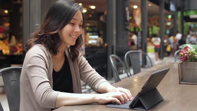 Asian Woman using Laptop in Shopping Mall
