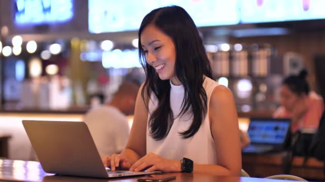 asiatische frau mit laptop arbeitet freiberuflich im cafe - bloggen stock-videos und b-roll-filmmaterial