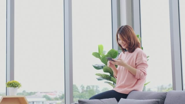 asian woman using mobile at comdominum video