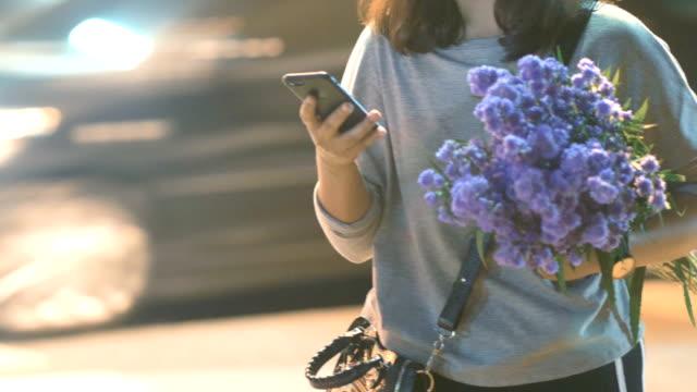 asiatisk kvinna använder mobiltelefon på natt city - blomstermarknad bildbanksvideor och videomaterial från bakom kulisserna