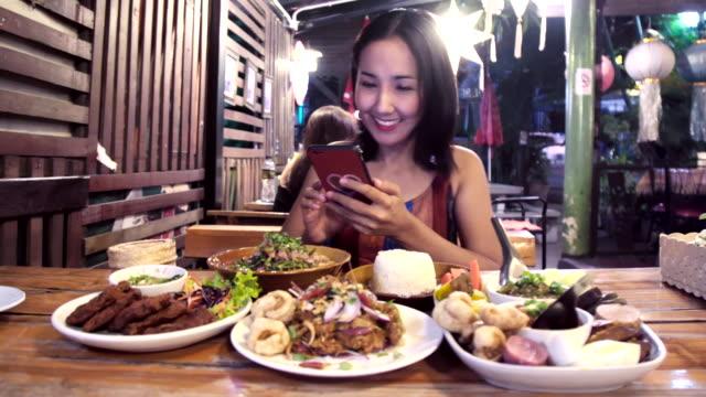 asian woman using mobile smart phone taking photo group of thai foods. - tajska kuchnia filmów i materiałów b-roll