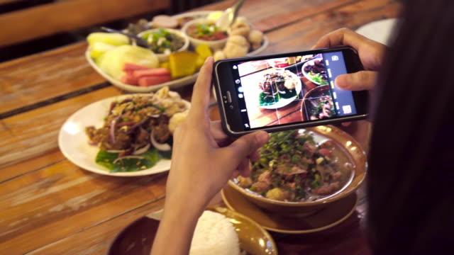 vidéos et rushes de femme asiatique utilisant le téléphone intelligent mobile prenant le groupe de photo des nourritures thaïlandaises. - vidéos de gastronomie