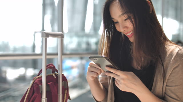 asian woman using on smart phone while waiting for her flight - business travel stock videos and b-roll footage
