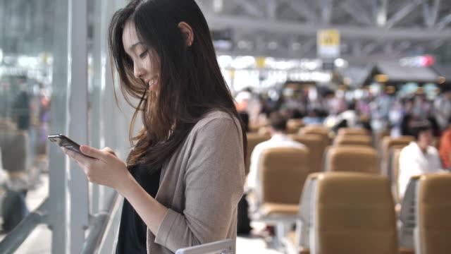 Asiatische Frau mit auf Smartphone während des Wartens auf ihren Flug – Video