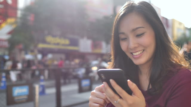 vídeos de stock e filmes b-roll de asian woman using phone in the city with sunset - mensagem sms