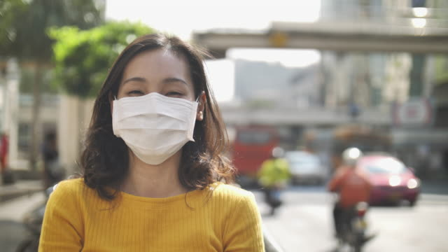 asian woman using pollution mask for protection from air pollution in big city - face mask stock videos & royalty-free footage
