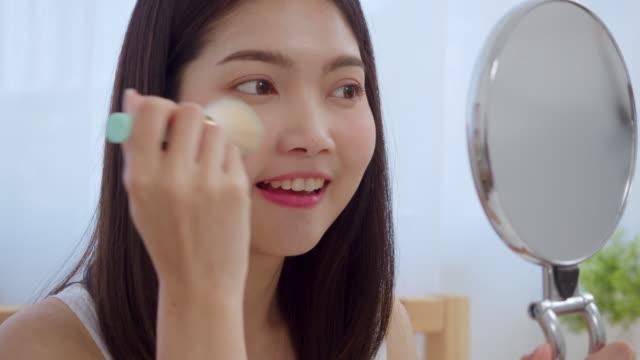 vidéos et rushes de femme asiatique utilisant la poudre par le pinceau composent dans le miroir avant, femelle heureuse utilisant des cosmétiques de beauté pour s'améliorer prête à travailler dans la chambre à coucher à la maison. concept de mode de vie de femmes à la - pinceau à maquillage