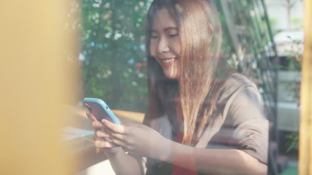 asiatische frau mit smartphone und lächelnd in café - smartphone mit corona app stock-videos und b-roll-filmmaterial