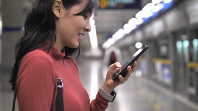 地下鉄駅でスマートフォンを使用してアジアの女性 - 通販点の映像素材/bロール