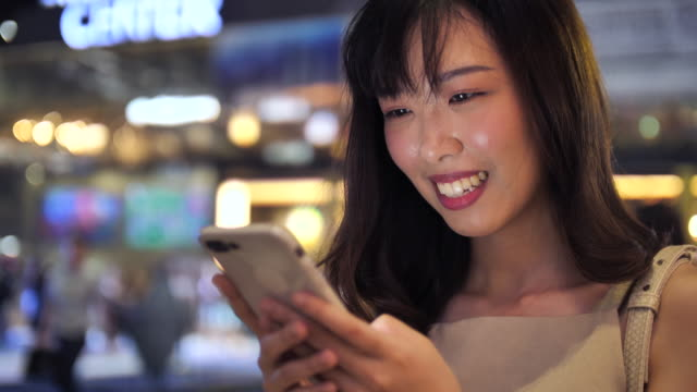 Asian Woman using Smart phone at night