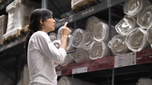 Asian Woman using Smart phone Check list in Warehouse, Order for Shipping
