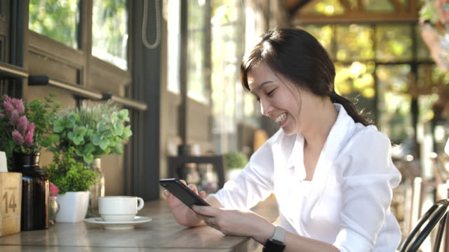 vídeos de stock, filmes e b-roll de mulher asiática que usa o telefone esperto no café - aromaterapia