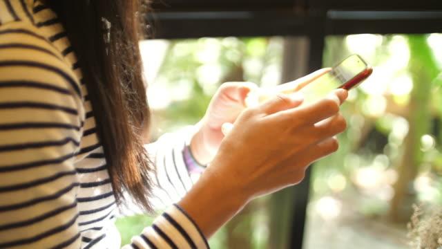 vidéos et rushes de femme asiatique utilisant le téléphone intelligent dans le café - 30 34 ans
