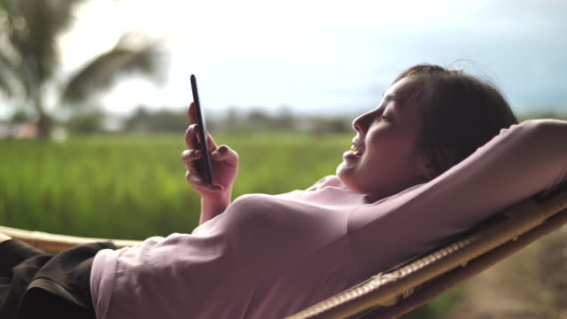 Asian Woman using Smart phone lying in the hammock on Sunset