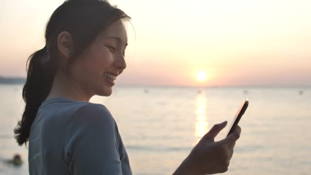 asian woman using smart phone on beach at sunset - woman chat video mobile phone video stock e b–roll