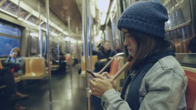 Asian woman using smart phone on subway train. Young beautiful woman uses the smartphone in public transportation, in metro. Girl surfing the Internet. New York. USA subway train stock videos & royalty-free footage