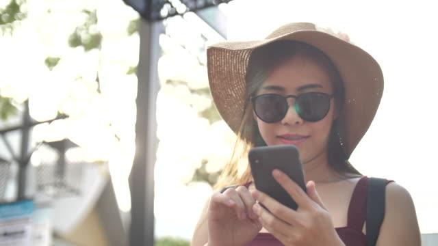 asian woman using smart phone - femminilità video stock e b–roll