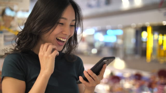 Asian woman using Smart phone Winning Concept celebrating success