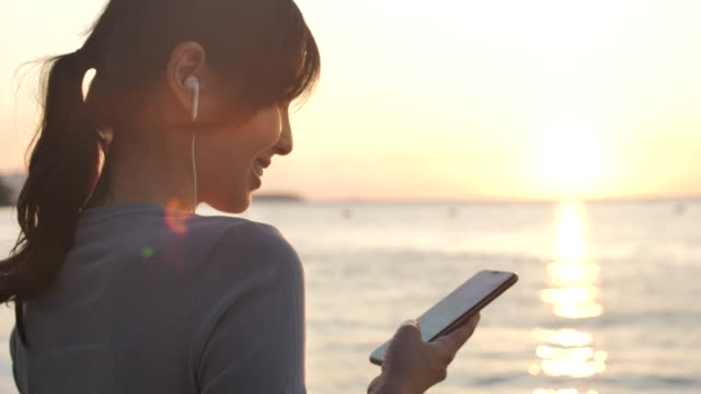Asian Woman using Smart phone with Earphone at sunset on Beach for her Vacation