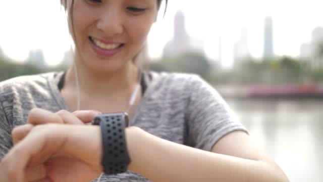 donna asiatica che usa smart watch per controllare il polso nell'esercizio fisico - computer indossabile video stock e b–roll