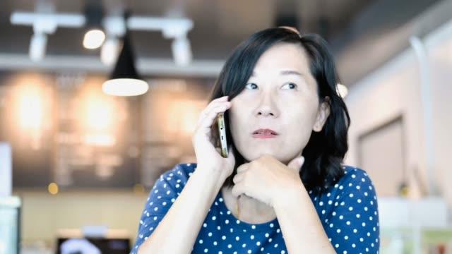 vídeos de stock e filmes b-roll de asian woman using smartphone in coffee shop near window, lifestyle - coffee table
