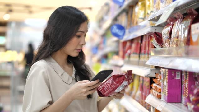 슈퍼마켓에서 스마트폰을 사용 하 여 아시아 여자, 슬로우 모션 - 쇼핑 스톡 비디오 및 b-롤 화면