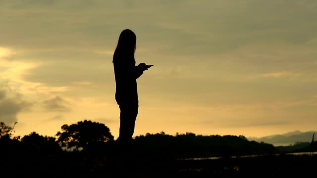 Asian woman using smartphone in the nature, Slow motion video
