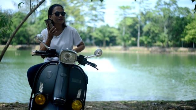 stockvideo's en b-roll-footage met aziatische vrouw met behulp van smartphone op scooter in de buurt van het meer. - s
