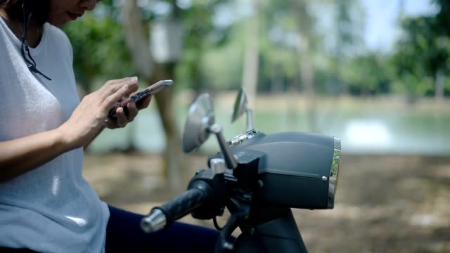 vídeos de stock e filmes b-roll de asian woman using smartphone on scooter near the lake - helmet motorbike