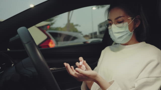 asian woman using wash hand alcohol gel pump dispenser in car - essential workers stock videos & royalty-free footage