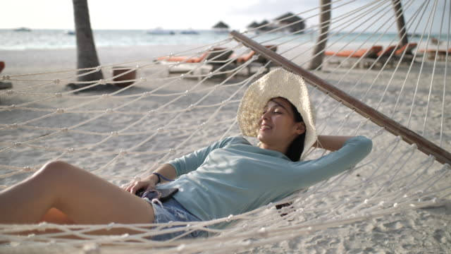 slow motion asian woman vacation in hammock at beach - amaca video stock e b–roll