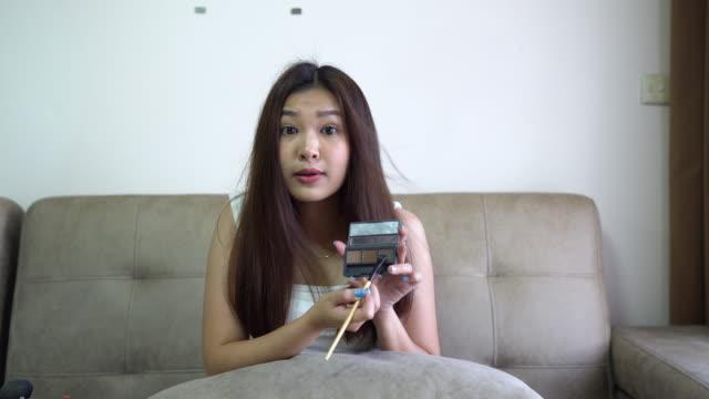 asiatische frau vlogging über sprechen make-up kosmetik zu hause studio. live, aufnahme, blogger, streaming - kosmetik beratung stock-videos und b-roll-filmmaterial