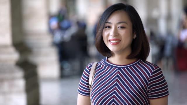 asian woman waiting for someone,smiling happy to the camera - happy holidays filmów i materiałów b-roll