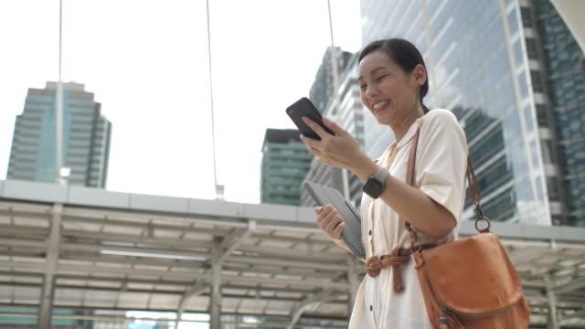 아시아 여자 산책 과 사용 그녀의 스마트 폰 에 도시 - 아시아인 스톡 비디오 및 b-롤 화면