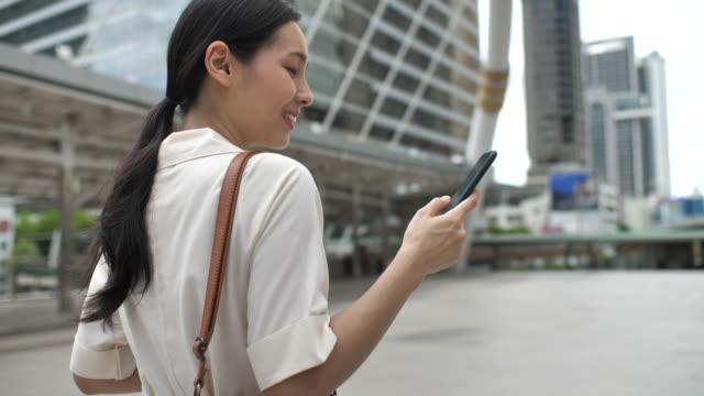 vídeos de stock, filmes e b-roll de mulher asiática que anda na cidade e que usa o telefone esperto - ásia