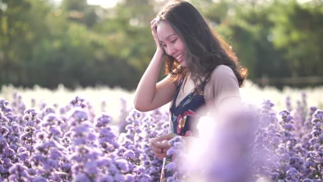 stockvideo's en b-roll-footage met aziatische vrouw wandelen op het gebied van bloem - floral line