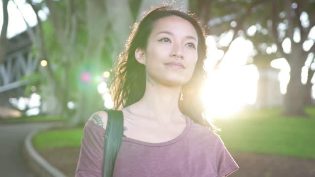 Mulher asiática, caminhadas ao ar livre e sorrindo - vídeo