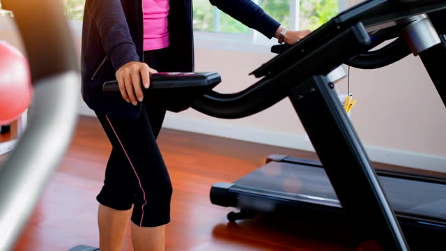 Asian woman walking,  running on treadmill gym workout. video