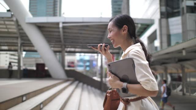 asiatische frau zu fuß mit spracherkennung am telefon in der stadt - bucht stock-videos und b-roll-filmmaterial