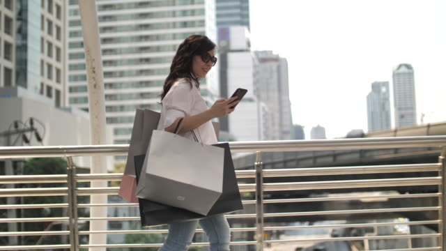Asian Woman walking with Shopping bag after Shopping day in City